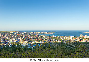 Scenic view of Gelendzhik city and sea bay. Sunrise time. Trees on hills on foreground. Vacation on resort.