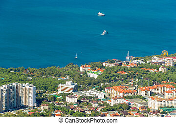 Scenic view of Gelendzhik city district and sea bay. Sunny day. Buildings, coast, ships in Black sea and horizon in frame.