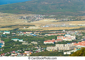 Scenic view of Gelendzhik resort city district from hill of caucasian mountains. Buildings, streets at the foot of the mountains.