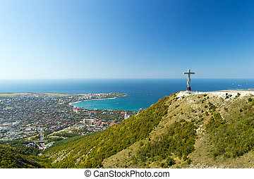 Scenic view of Gelendzhik resort city from hill of caucasian mountains. Worship cross monument with orthodox chapel in foundation on hill.