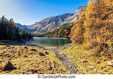 Scenic view of mountain lake at autumn sunny day. Europe, Austria, Tyrol, Lake Obernberg, Stubai Alps.