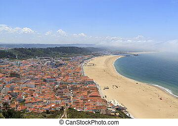 Scenic view of Nazare beach from the funicular. Coastline of Atlantic ocean. Portuguese seaside town on Silver coast. White houses and red tiled roofs Sea landscape of Nazare, Portugal