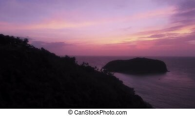 Scenic view of Phangan sunset, large black hill silhouette...