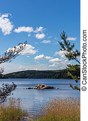 Scenic view of the stone shaman on Lake Tulmozero under a blue sky with clouds, Karelia. Russia