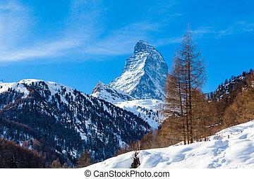 Scenic view on snowy Matterhorn peak in sunny day with blue sky. Switzerland