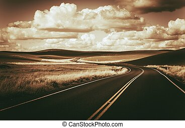 Scenic Winding Road and Butted Landscape in Dark Sepia Color Grading. Eastern Washington State, USA.