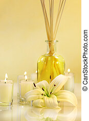Scented sticks with candles and lily on pale background