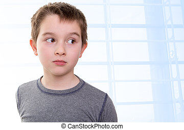 Eight years old kid looking out skeptically accusing with his big eyes