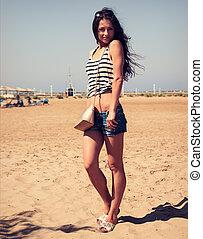 schöne , lächelnde frau, mit, mode, tasche, posierend, strand, hintergrund, in, jeansstoff, shorts., paßte, kontrast, porträt