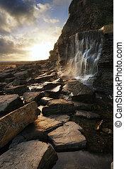 schöne , landschaftsbild, wasserfall, strömend, in, steinen, auf, sandstrand, an, sonnenuntergang