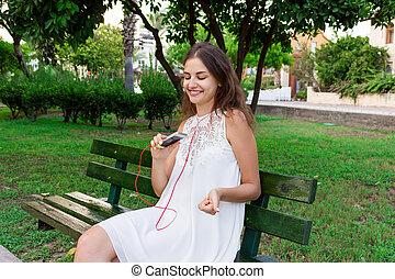 schöne , zuhören, beweglich, kopfhörer, park, junger, bank, musik, lachender, telefon, genießt, spaß, stilvoll, m�dchen, haben