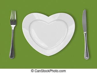 schaaltje, in vorm, van, hart, tafeel mes, en, vork, op, groene achtergrond