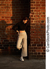 schaduw, lang, grijze , broek, roodharige, breed, taille, baksteen muur, licht, achtergrond, ondergaande zon , hoog, zonlicht, vervelend, meisje, black , verticaal, mooi, het poseren, rood, mouw, t-shirt, been, gieten, sensueel, jersey