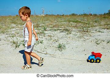 schattig, baby jongen, slepen, speelgoedauto, wandelende, op, de, akker