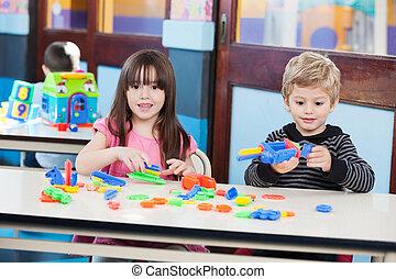 schattig, meisje, met, vriend, spelend, blokjes, op het bureau, in, klaslokaal