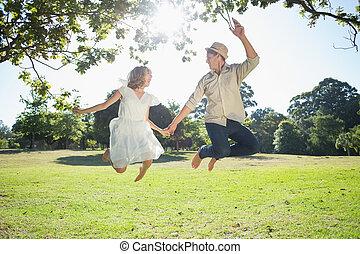 schattig, paar, park, samen, springt, holdingshanden