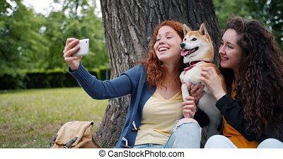 schattig, smartphone, meiden, boeiend, park, dog, fototoestel, gebruik, vrienden, selfie, vrolijke