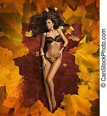 schattig, vrouw, het leggen, op, de, bladeren