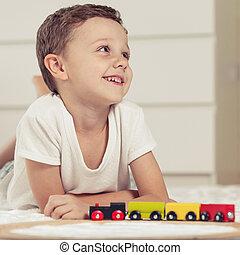schattige, jongetje, spelen met speelgoed, het liggen, op, de, floor.