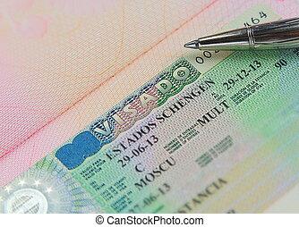 Schengen multi visa in passport with pen above