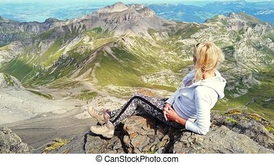 Tourist woman relaxing after hiking and looking the amazing panorama 360 degrees surrounding 200 peaks from Schilthorn viewpoint in Bernese Oberland, Jungfrau Region above Murren in Lauterbrunnen.
