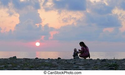 Schislivaya family: mother, baby son on the rocky sea beach during sunset. Parent play and kiss baby in the rays of the red sun and blue sky
