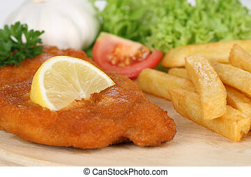 Schnitzel cutlet meal with french fries, lemon and lettuce ...