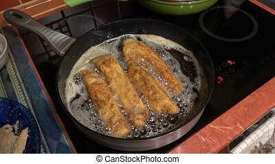 Schnitzel fried in the olive oil in a frying pan