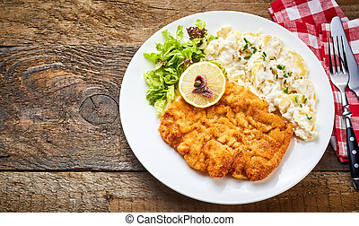 Schnitzel with side dish on rustic table