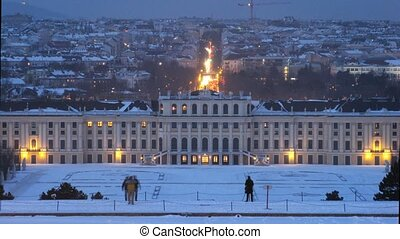 Schoenbrunn palace stands against evening city in night