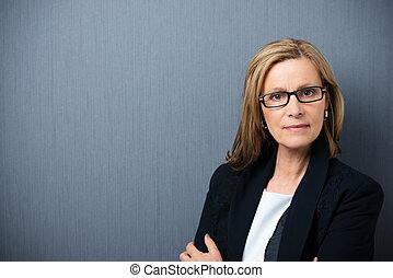 Scholarly looking middle-aged woman wearing heavy rimmed...