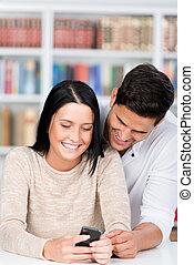 scholieren, gebruik, mobiele telefoon, samen, in, bibliotheek