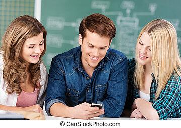 scholieren, huddled, samen, ongeveer, een, mobiele telefoon