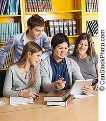 scholieren, met, digitaal tablet, het bespreken, in, universiteit, bibliotheek