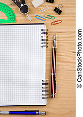 school accessories and checked notebook on wood