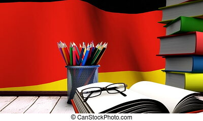 School accessories on a table with German flag floating