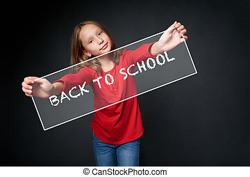 School age girl holding Back to school banner over dark...