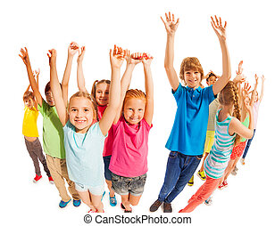 School age kids stand together with raised hands
