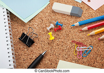 School and office supplies on cork wooden background