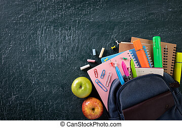 School backpack and school supplies with chalkboard background. Education or back to school concept.