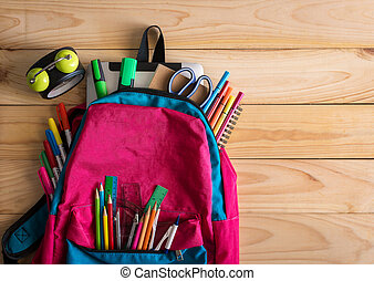 School backpack with school supplies and clock on wooden...