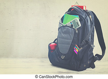 School backpack with supplies on white desktop, retro toned