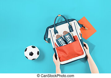 School backpack with trainers and ball on blue