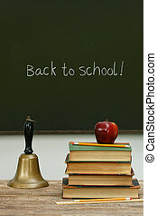 School bell and books on desk with chalkboard