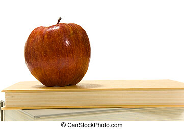 School books and apple against white
