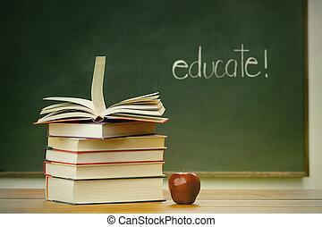 School books and apple on desk