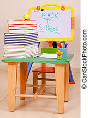 School books and apple on desk with sketchboard