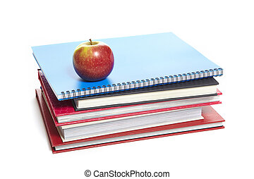 School books and apple on white background