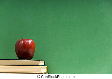 School books and chalkboard - School books and apple in...