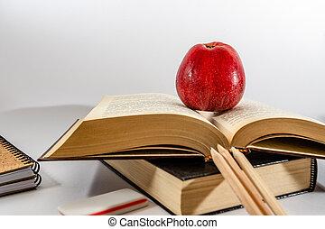 School books on desk. white background.